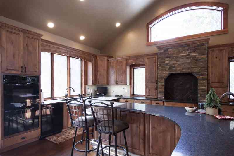 The island curves through the kitchen and has seating on one side and prep space on the other.