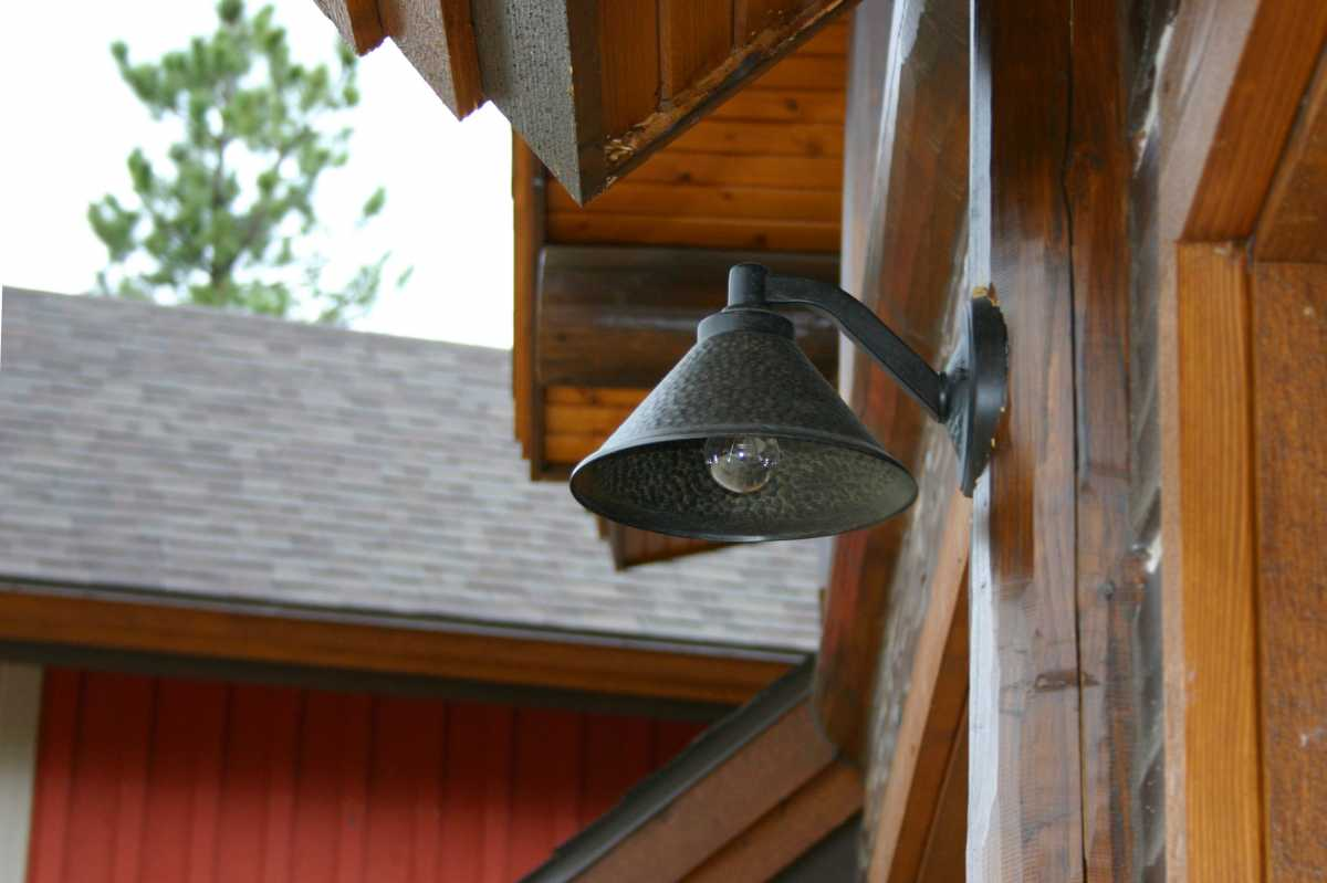 An exterior barn light cut to fit perfectly into the log siding.
