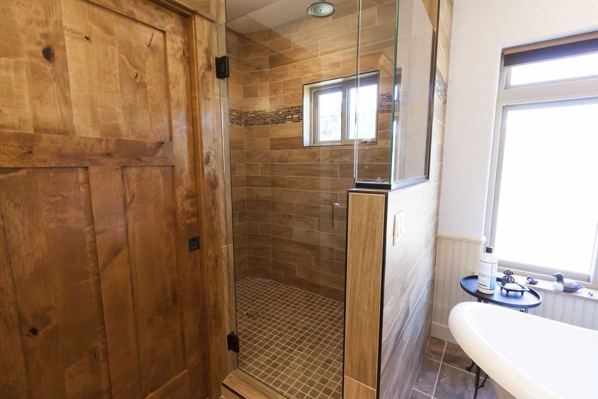 The master walk-in shower with a glass door and half glass-wall.
