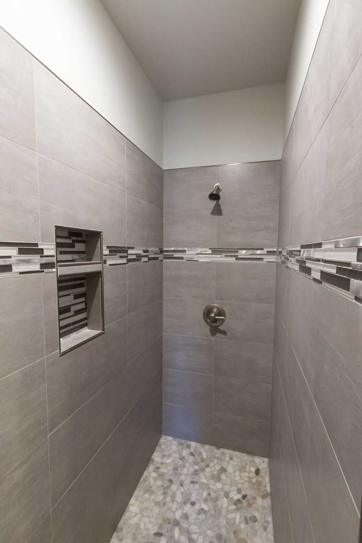 The tiled master shower and it's beautiful pebble flooring.