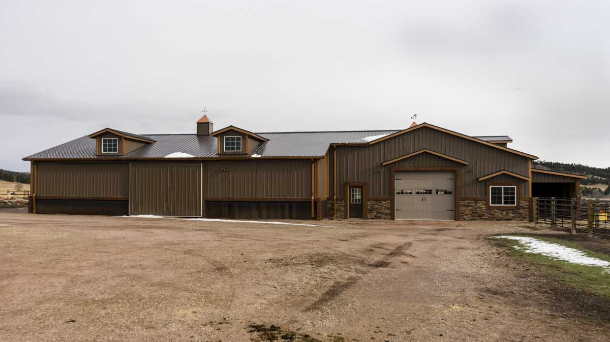 The back view showcases a large stable door and a sliding barn door.