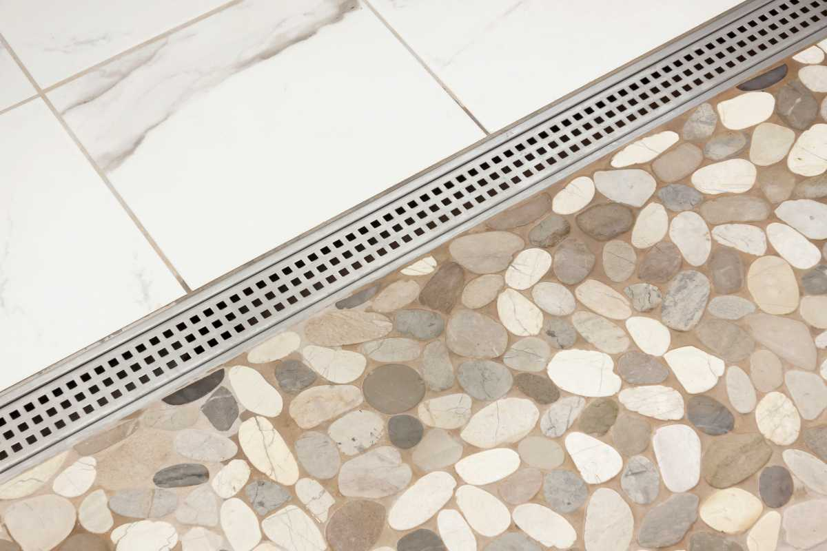 A detailed view of the horizontal shower drain and pebble tiling.