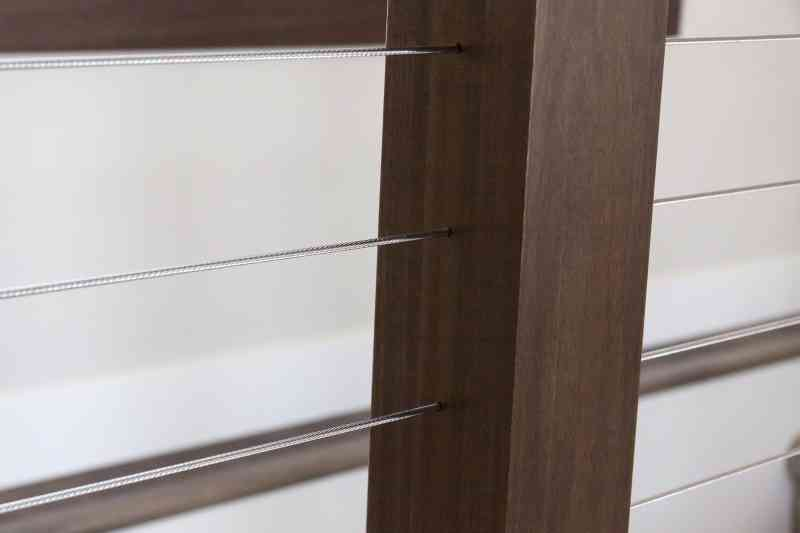 A detailed view of the sleek cable and wood post railing in the entryway.