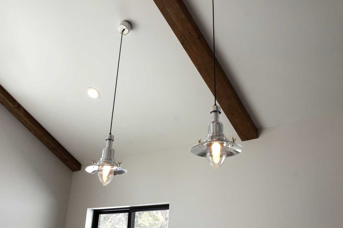 Farmhouse pendant lights hang over the dining table.
