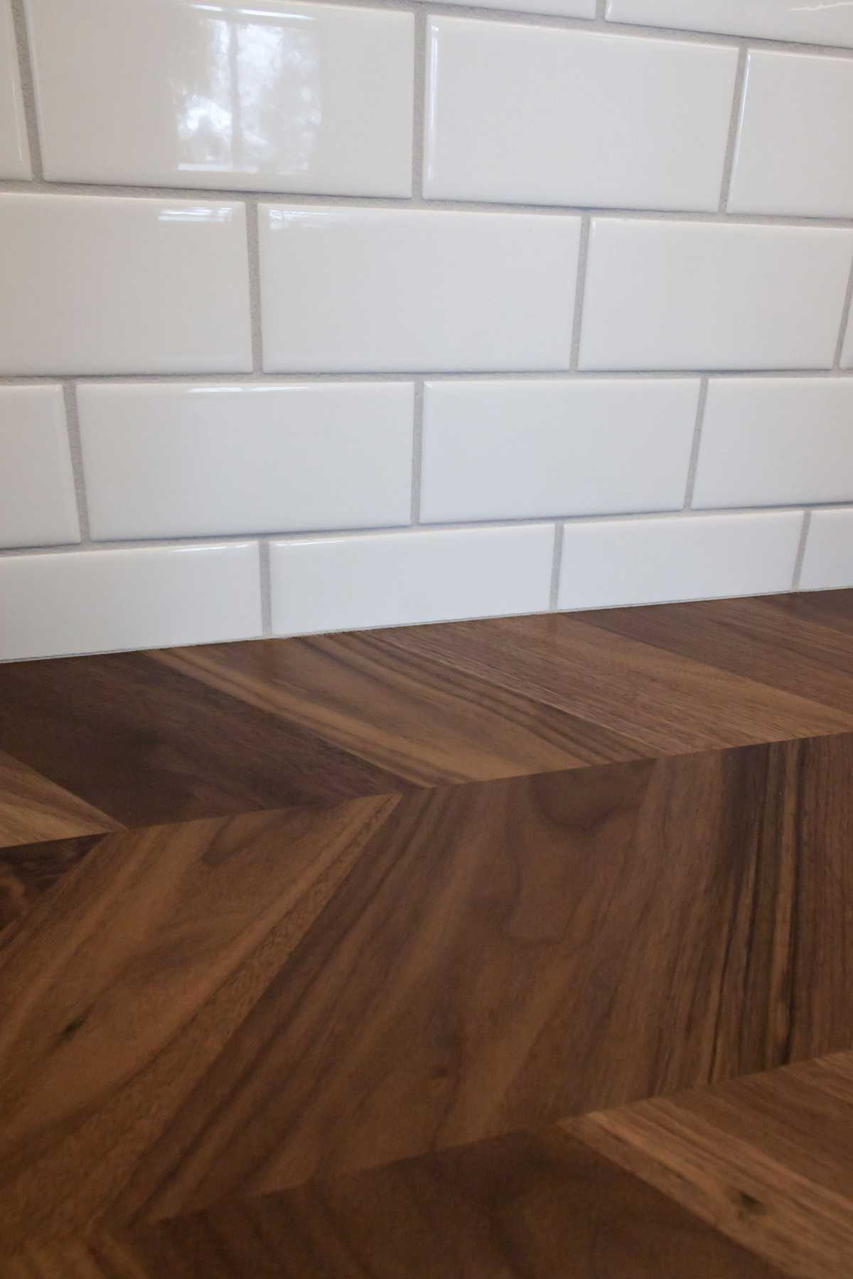 A detailed view of the white subway tile and gorgeous herringbone, wood countertops.