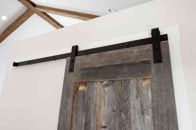 A custom-built, sliding barn door leading to the coat room.