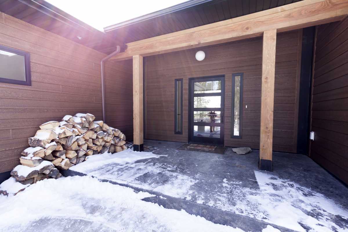 The home's entrance is framed by large timbers and a stamped concrete porch.