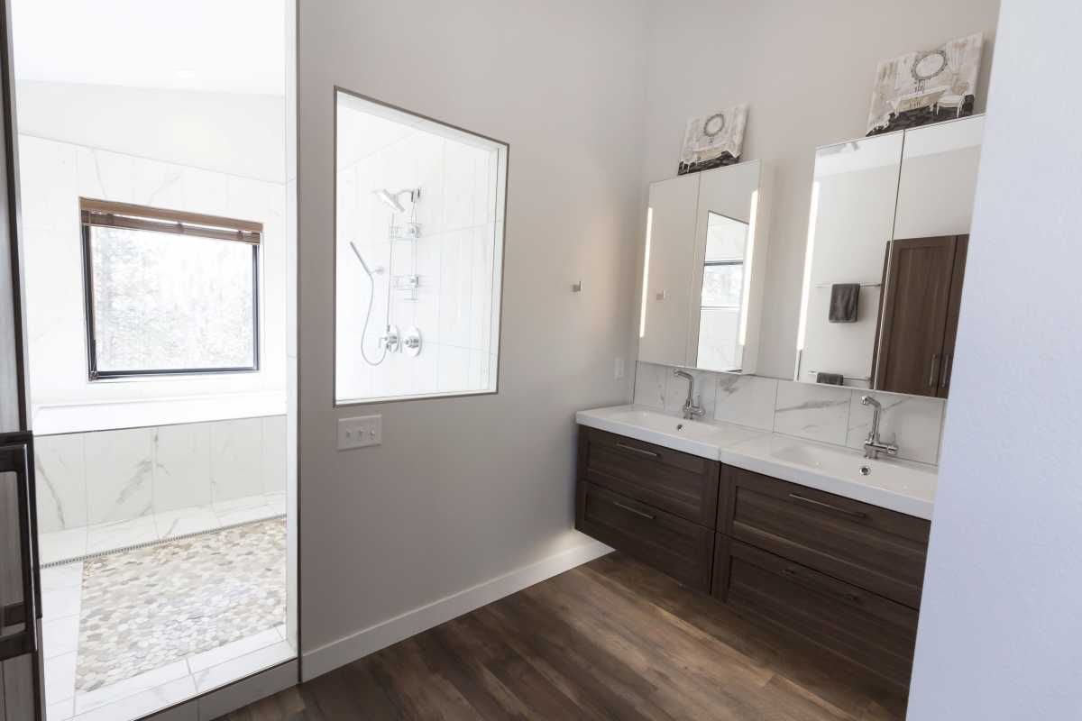 A glass opening in the bathroom brings in the natural light from the shower room's window.