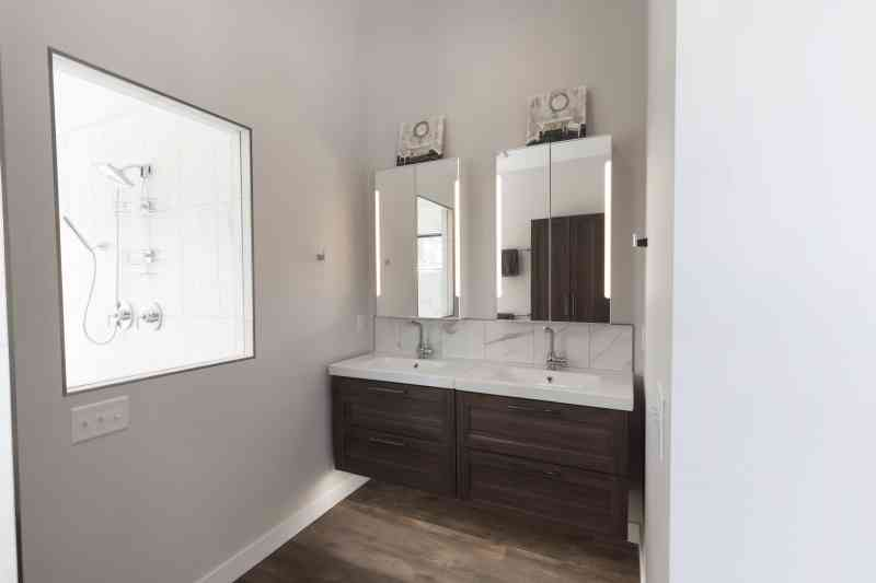 Modern, floating vanities in the master bath with built in lighting.